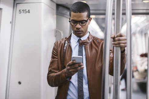 Businessman with smartphone on the subway train - EBSF000487