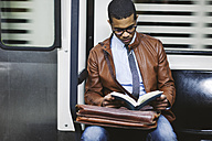 Businessman reading book on the subway train - EBSF000501
