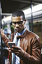 Portrait of businessman with smartphone and earphones hearing music on the subway train - EBSF000508