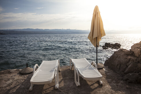 Croatia, view to Adriatic Sea with two sun loungers and a sunshade in the foreground - ANHF000012