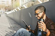 Businessman sitting outside using mini tablet - EBSF000524