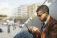 Businessman sitting outside using mini tablet - EBSF000525