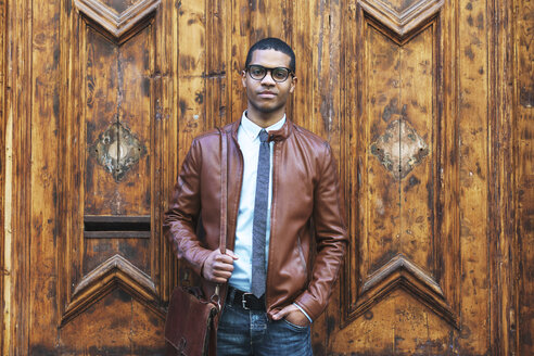 Portrait of businessman wearing leather jacket and glasses in front of wooden door - EBSF000529