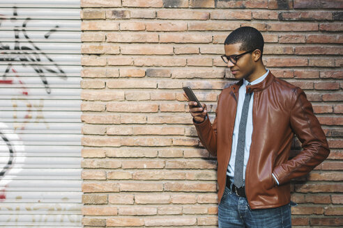 Businessman with smartphone wearing leather jacket and glasses in front of brick wall - EBSF000531