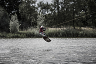 Germany, Garbsen, wakeboarder at Blue Lake jumping in the air - GCF000054