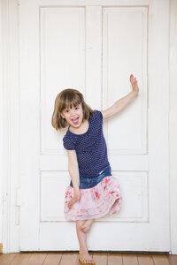 Happy girl dancing at wooden door - LVF003154