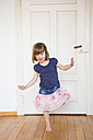Girl dancing at wooden door - LVF003155