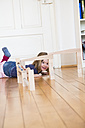 Little girl lying on floor behind marble run - LVF003147