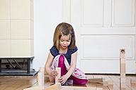 Little girl crouching on floor playing with wooden building bricks - LVF003149