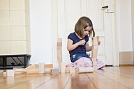 Little girl crouching on floor playing with wooden building bricks - LVF003151
