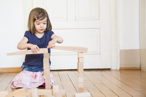 Little girl crouching on floor playing with wooden building bricks - LVF003153