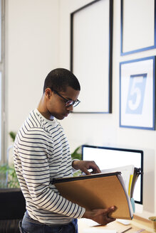 Young creative man with files in his home office - EBSF000547