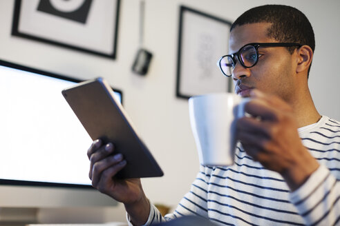 Young creative man with mini tablet having coffee break in his home office - EBSF000558