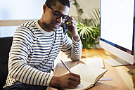Young creative man telephoning with smartphone at desk while writing in his notebook - EBSF000557