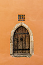 Germany, Passau, historic wooden door of an old building with orange facade - EJWF000739