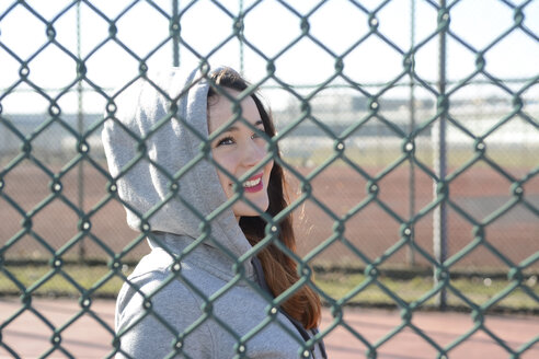 Portrait of woman wearing hooded jacket behind mesh wire fence - BFRF001066