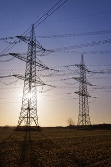 Germany, North Rhine-Westphalia, Grevenbroich, power pylons against the morning sun - GUFF000098
