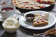 Strawberry rhubarb tart with whipped cream and cup of fruit tea - YFF000366