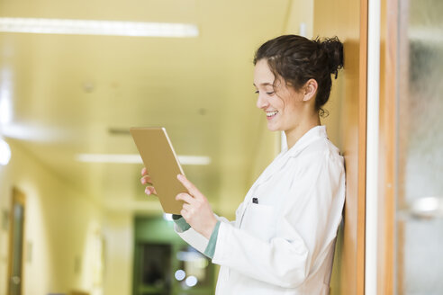 Smiling young doctor with digital tablet on hospital floor - DISF001614
