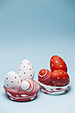 Coloured Easter eggs in paper cups in front of light blue background - BZF000129