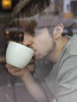 Young man behind windowpane drinking coffee - HCF000116
