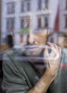 Young man looking through windowpane - HCF000118