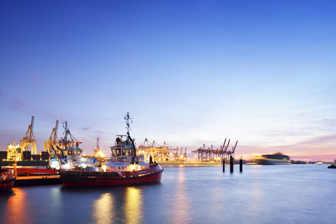 Germany, Hamburg, container harbor Waltershof with tugboats at blue hour - BR001168