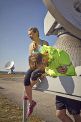 Germany, Raisting, young jogger couple having a rest at ground station - KDF000707