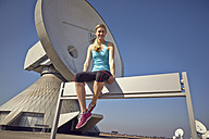 Germany, Raisting, young female jogger having a rest at ground station - KDF000708