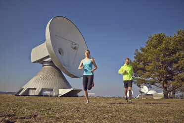 Germany, Raisting, young couple jogging at ground station - KDF000715