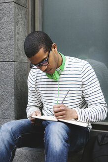 Young man with green headphones sitting outside writing something in his notebook - EBSF000560
