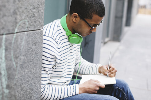 Young man with green headphones sitting outside writing something in his notebook - EBSF000562
