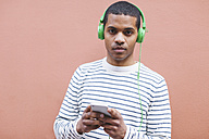 Portrait of young man hearing music with green headphones - EBSF000568