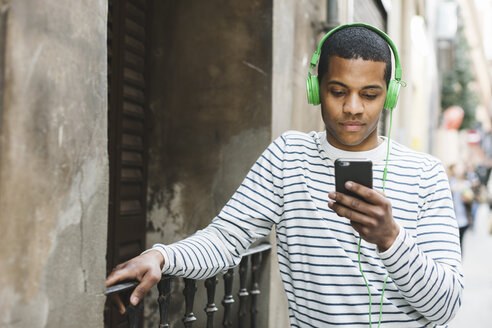 Spain, Barcelona, young man hearing music with green headphones on street - EBSF000573
