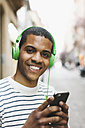 Portrait of smiling young man hearing music with green headphones on street - EBSF000576