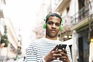 Spain, Barcelona, portrait of smiling young man hearing music with green headphones on street - EBSF000578