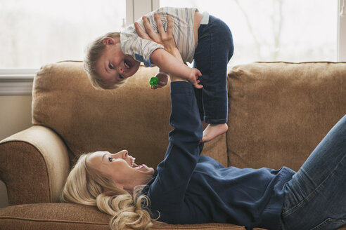 Mother lifting little son while lying on couch - SELF000040