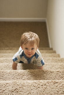 Portrait of little boy learning to go up a staircase - SELF000031
