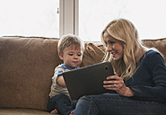 Mother and little son sitting on couch using digital tablet together - SELF000043