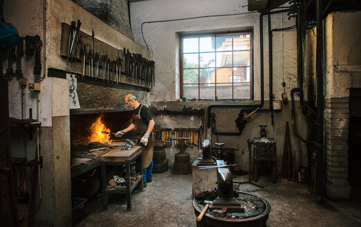 Senior blacksmith working in hammer mill - HHF005316