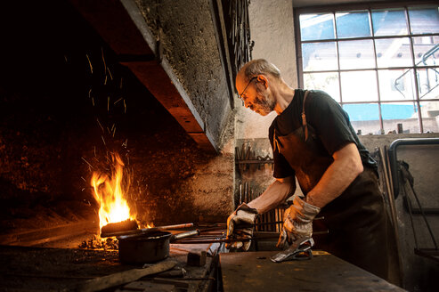 Senior blacksmith working in hammer mill - HHF005318