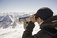 Germany, Bavaria, woman looking through telescope at Zugspitze - FLF001027