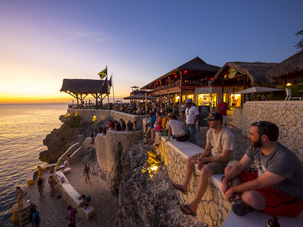 Jamaica, Negril, people at Rick's Cafe at the coast at sunset - AM003951