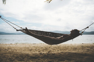 Philppines, Visayas, Woman wearing bikini relaxing on a hammock in the evening - GEMF000190