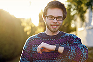Portrait of smiling young hipster with smartwatch - BRF001185