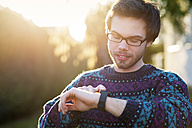 Portrait of young hipster using smartwatch at backlight - BRF001186
