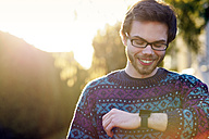 Portrait of smiling young hipster looking at his smartwatch - BRF001187