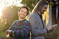 Two laughing hipsters with smartwatch and smartphone - BRF001192
