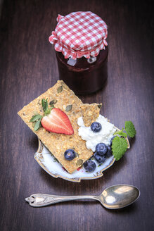 Jam jar, slice of crispbread, curd and fruits on wood - VTF000416