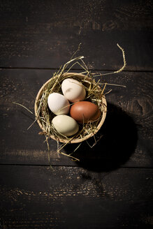 Easter nest with eggs in bowl on dark wood - MAEF010241